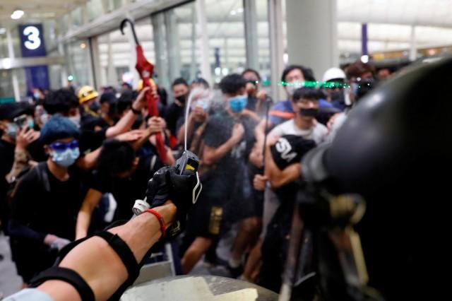 Hong Kong airport services suspended anew, protesters clash with police